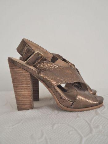 Sandalias de tacón grueso en color dorado.